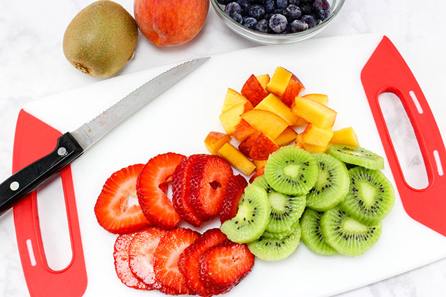 Cut up fruit to make homemade fruit popsicles