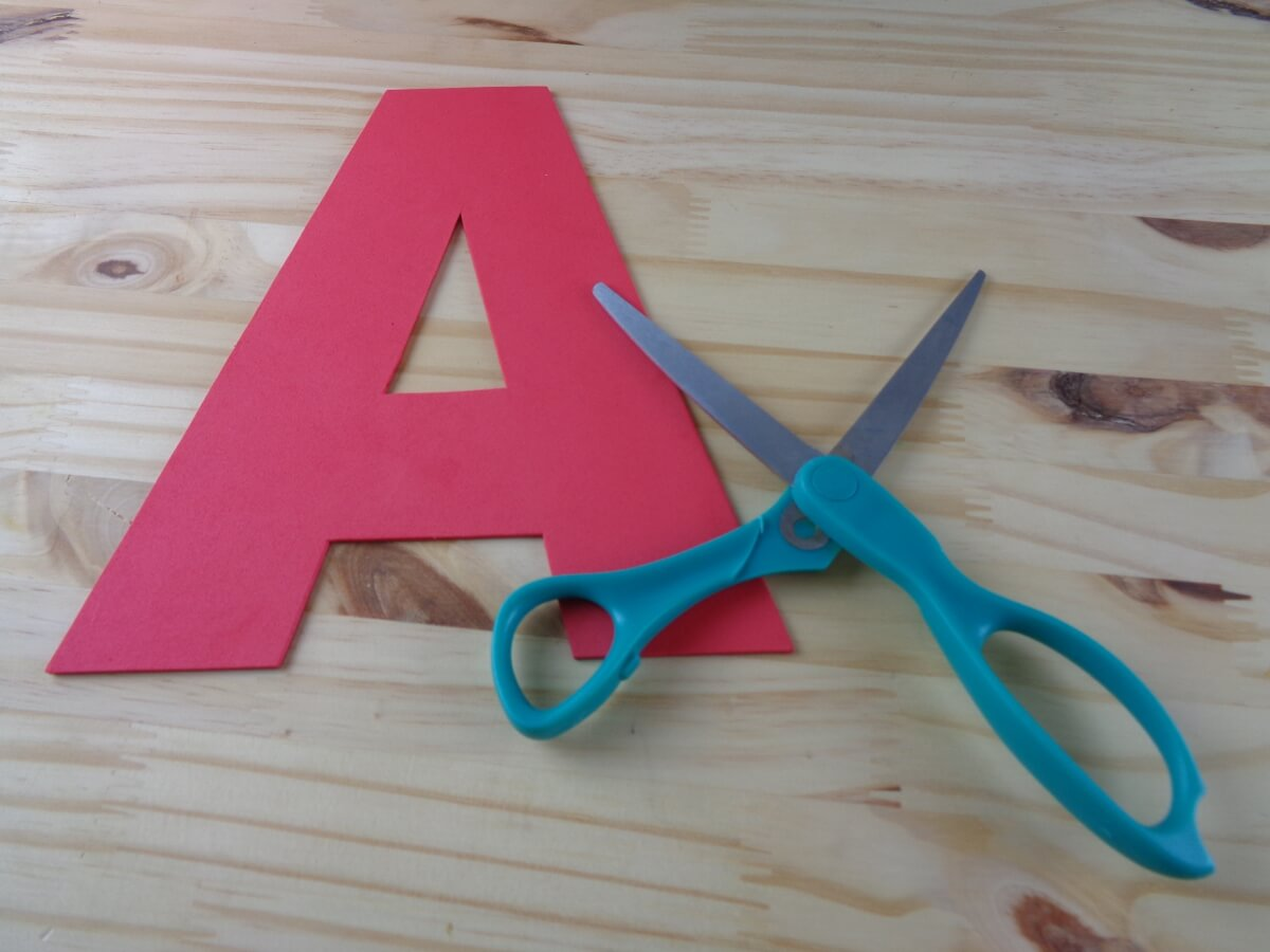 cut a white triangle large enough to cover the opening of the a glue onto the back of the letter